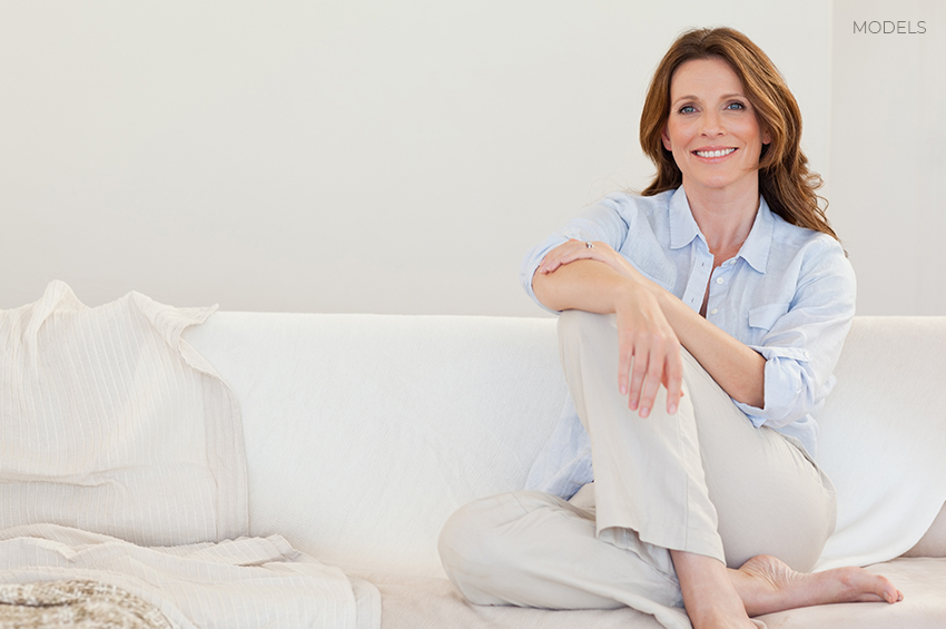 Middle-Aged-Woman-Casually-Sitting-on-Couch-Smiling