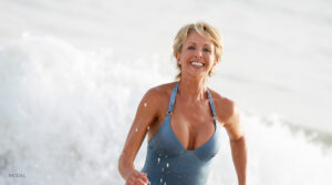 Middle Aged Woman with Curvaceous Figure Running on the Beach
