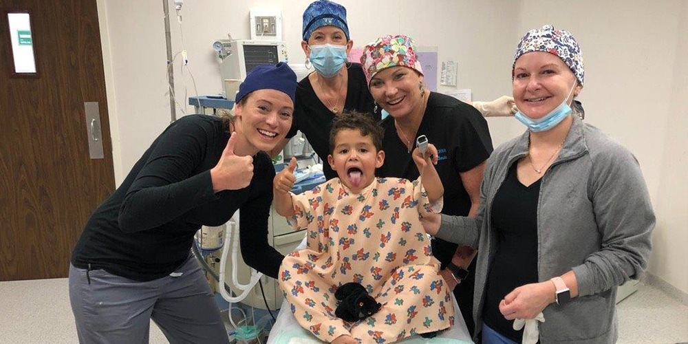 Group Photo of Surgical Team with a Joyful Young Boy in the Surgical Room